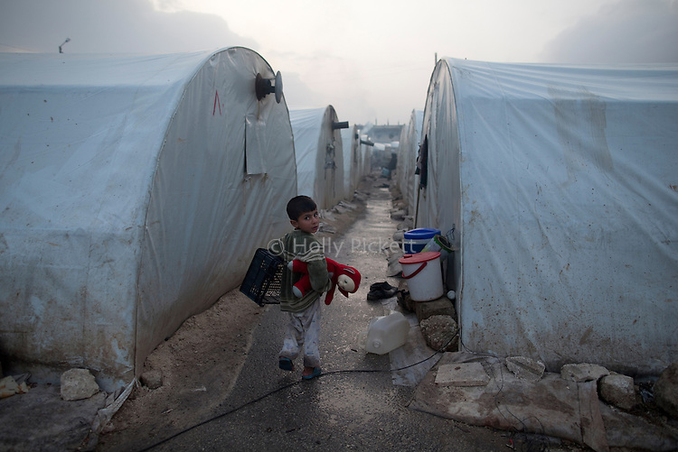 A Syrian boy walks through Azaz Camp, just inside the Syrian border with Turkey, Feb. 23, 2013. According to administrators, this camp holds roughly 9,000 to 10,000 internally displaced persons (IDP's). Two meals per day are provided by a Turkish humanitarian organization, and Qatar Red Crescent provided tents. There is very little electricity, and no running water. There is also a refugee camp on the Turkish side of the border, but it is full. The UN Refugee Agency has reported a sharp increase in refugees fleeing Syria for neighboring countries in the first months of 2013.
