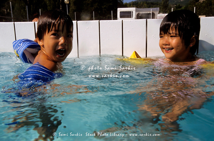 Two young children swimming in a pool with armbands.