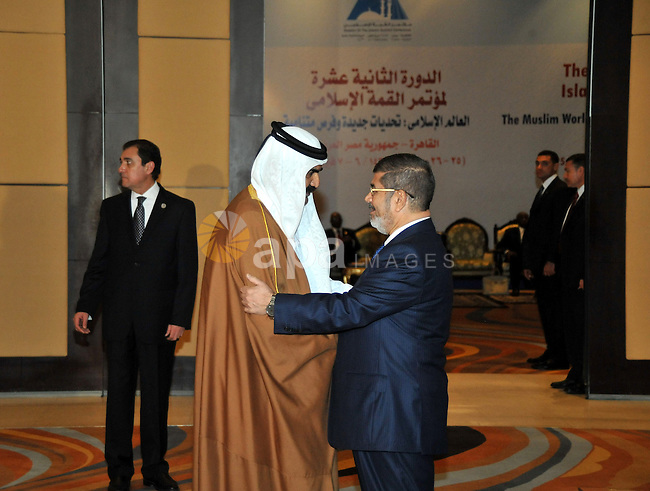 A handout picture released by the Egyptian presidency shows Egyptian President Mohamed Morsi (R) greeting Qatari Emir Sheikh Hamad bin Khalifa al-Thani during the 12th summit of the Organisation of Islamic Cooperation (OIC) in Cairo on February 6, 2013. The 12th OIC summit opened in Cairo, with Syria's civil war and the battle against Islamist militants in Mali topping the agenda. The meeting gathers the leaders of 26 of the OIC's 57 states, including the presidents of Iran and Turkey. Photo by Egyptian presidency