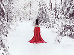 Beautiful half nude woman with bare back in red kimono walking away into a snowy winter scenery