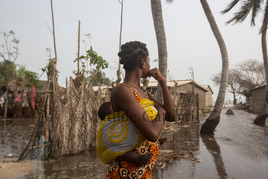 Ghana -  Fuveme - A villager stands next to her house as the Ocean water rises in the streets. <br /> Nestled between the ocean and the Volta river estuary, the village of Fuvemeh has seen its territory reduced from several kilometers to few hundred meters. Nowadays, the villages sits on a narrow strip of land which separates the coastline from the adjacent lagoon. Haunted by coastal erosion, its 1,000 inhabitants have literally nowhere to move.