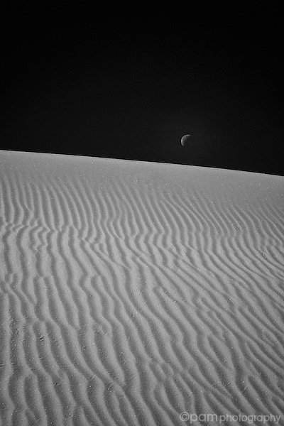 Monochrome image of moon rising over white sand dunes
