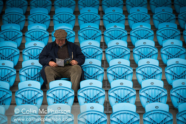 A solitary away fan reading the programme pre-match as Guernsey take on Corinthian-Casuals in a Isthmian League Division One South match at Footes Lane. Formed in 2011, Guernsey FC are a community club located in St. Peter Port on the island of Guernsey and were promoted to the Isthmian League Division One South in 2013. The visitors from Kingston upon Thames won the fixture by 1-0, watched by a crowd of 614 spectators.