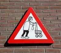 Verkeersbord  met een tekening van een oudere vrouw met een rollator/ boodschappenkar