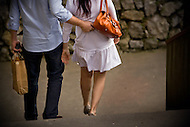 A young couple carries shopping bags after a long day shopping in Italy.