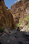 Hiking the Closed Canyon trail through a narrow slot canyon cutting through the Colorado Mesa to the Rio Grande River in the Big Bend area of Texas