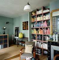 The blue sitting room has a retro feel with a variety of seating. Books and magazines are neatly arranged on an open shelving unit.