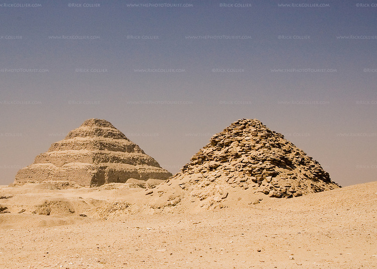 The desert at Saqqara, Egypt, is dotted with pyramids.  Here a much newer pyramid that has begun to collapse stands in the foreground, with the famous 'Step Pyramid of Zoser (or Djoser, or Doser) in the background.  Zoser's pyramid is among the oldest pyramids in Egypt, was designed and built by Imhotep, who was the pharoe's architect.  The 'step pyramid' style predates the more famous smooth-sided pyramids found in Giza. © Rick Collier.......Egypt Egyptian Cairo Saqqara pyramid pyramids step steps pharoah pharoahs Zoser Dozer Doser Djoser 'step pyramid' Imhotep tourist tourism history historic antiquities 'ancient Egypt' ancient antiquity audience tomb tombs
