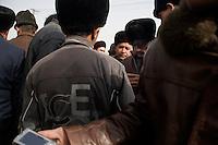 Uighur men bargain for used mobile phones in Kashgar, Xinjiang, China.
