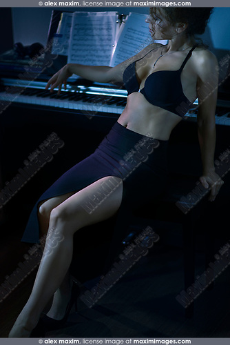 Beautiful woman in a sexy black skirt with a revealing cut and underwear leaning back against a piano keyboard in a dimly lit room