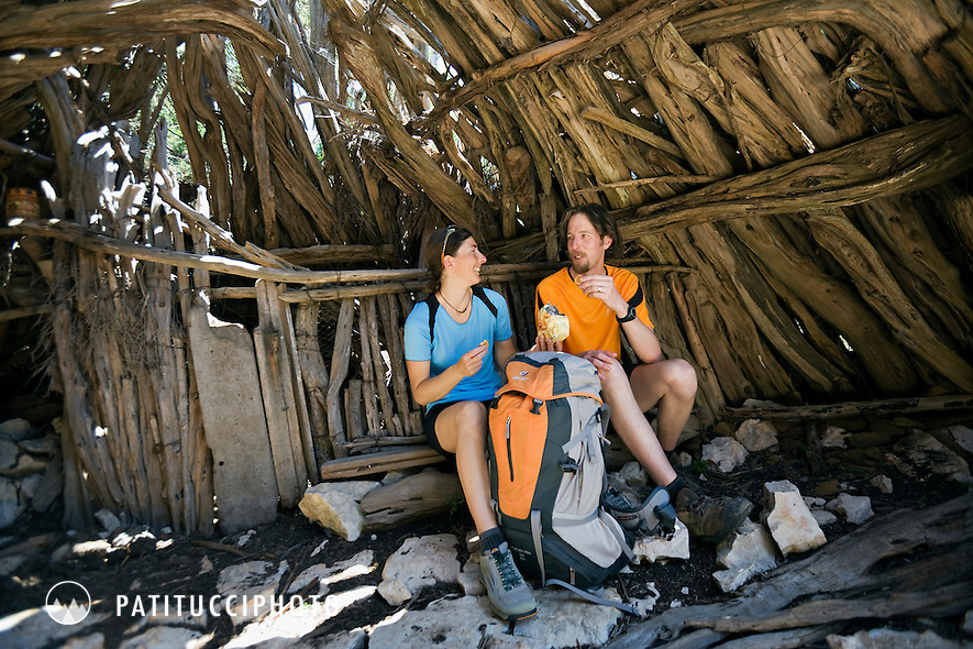 Tim Neville and Janine Patitucci hiking Sardinia's most famous hike, the Selvaggio Blu, known as Italy's most remote hike. The couple is taking a break in one of the many ancient shepherd shelters along the trail