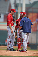 Harrisburg Senators pitching coach Chris Michalak (31) talks with pitcher Lucas Giolito (44) and catcher Pedro Severino (4) during a game against the Erie Seawolves on August 30, 2015 at Jerry Uht Park in Erie, Pennsylvania.  Harrisburg defeated Erie 4-3.  (Mike Janes/Four Seam Images)