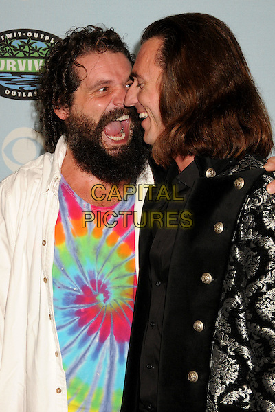 "RUPERT BONEHAM & BENJAMIN WADE .""Survivor"" 10 Year Anniversary Party held at CBS Studios, Los Angeles, California, USA, 9th January 2010..half length white shirt mouth open funny beard facial hair profile rainbow tie dye multi-coloured vest top shirt  .CAP/ADM/BP.©Byron Purvis/AdMedia/Capital Pictures."