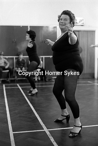 overweight woman keeping fit exercise class wearing high heal shoes Essex England 1980s