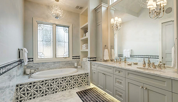 This custom bathroom features an Edie bathtub surround and border. Edie, a handmade mosaic, is shown in Nero, Bardiglio, Thassos and Carrara and is part of the Silk Road Collection by Sara Baldwin for New Ravenna.<br />