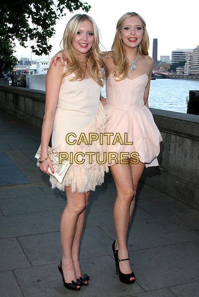 SAM & AMANDA MARCHANT .Samantha & Amanda Marchant Birthday Party arrivals at Temple Pier, London, England..June 25th, 2009.full length samanda sisters siblings twins pink white cream strapless dress feather clutch bag black sandals arm over peach shoulder .CAP/ROS.©Steve Ross/Capital Pictures.