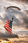 Skydiver with American flag with dramatic sky.