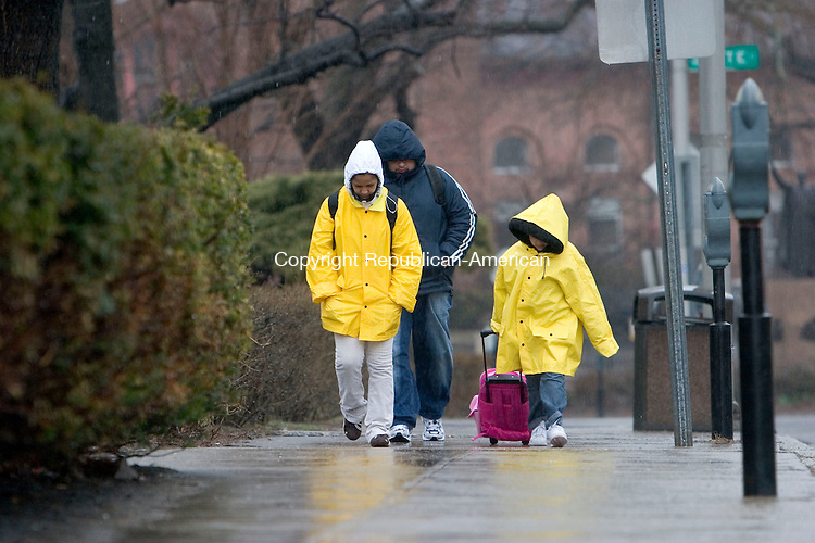 WATERBURY, CT- 15 APRIL 07- 041507JT08- <br /> Three people who did not want to be identified keep their heads down trying to stay dry in the rain as they walk up Grand Street in Waterbury on Sunday as a Nor'easter blew through the area with strong winds and excessive rain. <br /> Josalee Thrift Republican-American