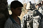 A young man glares as U.S. soldiers with Battery B, 2nd Battalion, 15th Field Artillery Regiment and Iraqi troops leave after searching his family's farm, during a sweep for insurgents and weapons caches south of Mahmudiyah, Iraq.  July 11, 2007. DREW BROWN/STARS AND STRIPES