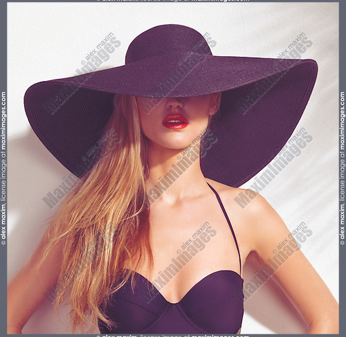 Beautiful young woman wearing a black sunhat covering her face and a swimsuit isolated on white wall background