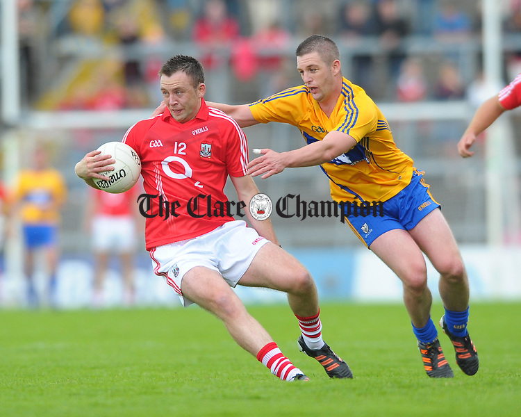 Paul Kerrigan of Cork in action against Enda Coughlan of Clare during the Munster senior football final at The Gaelic Grounds, Limerick. Photograph by John Kelly.