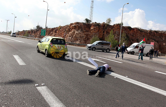 Israeli settlers run over a Palestinian activist by his car during a sit-in to block the road between Ramallah and Nablus to protest against Israel's military action on the Gaza Strip, on November 19, 2012 in the West Bank village of Silwad . Israeli air strikes across the Gaza Strip killed 13 people, raising the Palestinian death toll to 90 as Israel's relentless air campaign entered its sixth day. Photo by Issam Rimawi