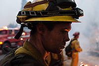 A weary firefighter stares  into the flames while working a 24-hour shift of conducting firing operations along US Route 50 near the town of Pollock Pines, California, USA, on 18 September 2014. Fire crews around California fight 12 major fires across the state, including the King Fire, located 56 miles (90 kilometers) east of Sacramento, California, which more than doubled in size overnight to 70,994 acres (28,730 hectares) and 5% contained.