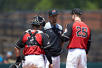 Hickory Crawdads pitching coach Jose Jaimes (center) has a meeting on the mound with relief pitcher Nick Snyder (25) and catcher Matt Whatley (19) during the game against the Charleston RiverDogs at L.P. Frans Stadium on May 13, 2019 in Hickory, North Carolina. The Crawdads defeated the RiverDogs 7-5. (Brian Westerholt/Four Seam Images)