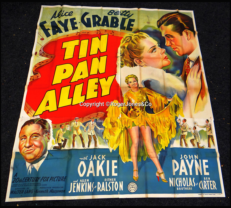 BNPS.co.uk (01202 558833)<br /> Pic: RogerJones&Co/BNPS<br /> <br /> Tin Pan Alley, 1940.<br /> <br /> A rare collection of 1930s and 40s cinema posters discovered by two builders after they were used as carpet underlay have sold for a whopping £75,000.<br /> <br /> More than half the total was made on a single poster, John Wayne's breakthrough film Stagecoach (1939), which sold for £31,000.<br /> <br /> The classic Hollywood movie posters, which were in near pristine condition, are from the halcyon days of cinema and included well known names such as Alfred Hitchcock, Sir Laurence Olivie and Boris Karloff.<br /> <br /> Before the sale auctioneers Rogers Jones & Co said it was difficult to predict what the posters would sell for as no comparisons had ever come to market but the collection of about 120 posters was expected to fetch several thousands.<br /> <br /> Two builders made the discovery in 1985 when they were renovating the home of a local cinema owner who had died in Penarth, south Wales.