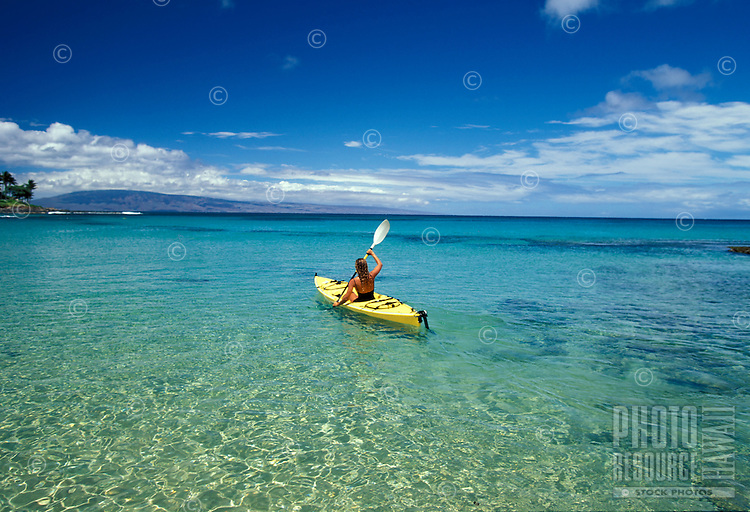 A woman heads out in a kayak at Napili Bay, Maui.