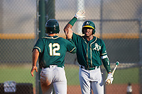 AZL Athletics Green Gavin Jones (12) is congratulated by Jorge Romero (23) after scoring a run during an Arizona League game against the AZL Reds on July 21, 2019 at the Cincinnati Reds Spring Training Complex in Goodyear, Arizona. The AZL Reds defeated the AZL Athletics Green 8-6. (Zachary Lucy/Four Seam Images)