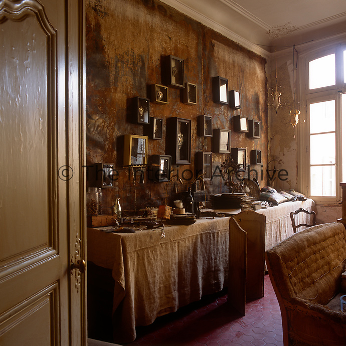 A view into a room with a wall hung with a fabric wall hanging. Wooden framed storage boxes are displayed on the wall above a long table cluttred with various items.