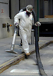 Workers wear protective gear while cleaning the streets in lower Manhattan days after the Sept. 11th attack.