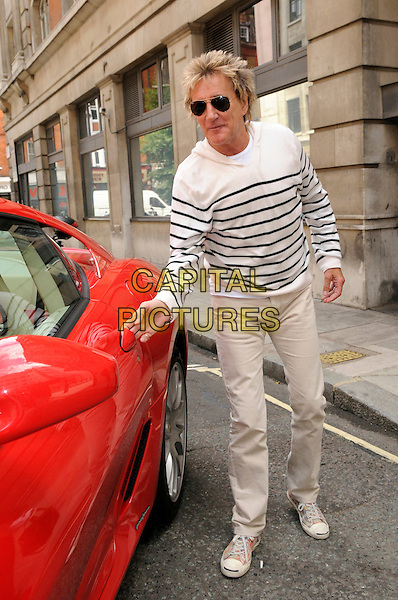 Rod Stewart.At BBC Radio 2, London, England..June 9th, 2011.full length red car ferrari length white stripe top sunglasses shades  black beige khaki trousers  .CAP/IA.©Ian Allis/Capital Pictures.