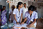 21 May 2013, Mandiganal Village, Karnartaka, India:  Nurses  Anita Poojara (26 at left) and Chitragowda Golda (26) of the Karnataka Mobile Health Clinic project  helping record patients details at  Mandiganal Village outside of Hubli. Assisting him is nurse Anita Poojara  (26) and accredited social health activist (ASHA) Renuka  Baramappa who refers patients to the project. The World Bank is financing the Karnataka Health Systems Project that is bringing mobile health clinics to remote villages in Karnataka and covers the cost of an ambulance, a doctor, pharmacist, two nurses, a cleaner and a driver. Villagers have the opportunity to see a doctor once a week for basic services and will be referred to Primary Health Care centres for larger issues Picture by Graham Crouch/World Bank