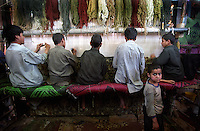 Afghan boys weave carpets in the space where they also eat and sleep in Peshawar, North-West Frontier Province. During the freezing winters they migrate from the mountains of Afghanistan to the factories of Peshawar and return home during the summer.