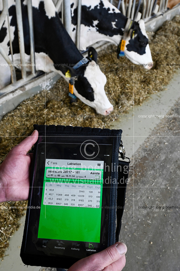 GERMANY, Echem, smart dairy cow milk farm, digitalization of agriculture, milk cows in stable, wearing sensor and reporting chips for robot milking, work with tablet / DEUTSCHLAND, Landwirtschaftlichen Bildungszentrum (EBZ) in Echem, Digitalisierung im Kuhstall und Melkstand, Milchkühe tragen Sensoren und Melder für den Melkroboter, Arbeit mit Tablet