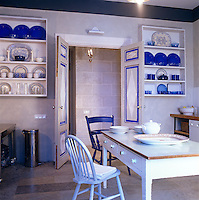 A matching pair of shelves displays a collection of ultramarine china creating a decorative focal point in this St Petersburg kitchen