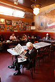 USA, California, San Francisco, a man ready the newspaper at a table inside Cafe Trieste, North Beach