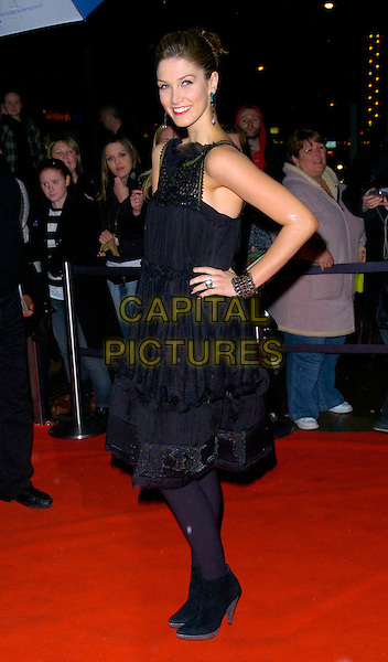 DELTA GOODREM.Arrivals - Emeralds & Ivy Ball, The Roundhouse, .London, England, December 1st 2006..full length black dress tights ankle boots bracelet ring hand on hip.CAP/CAN.©Can Nguyen/Capital Pictures