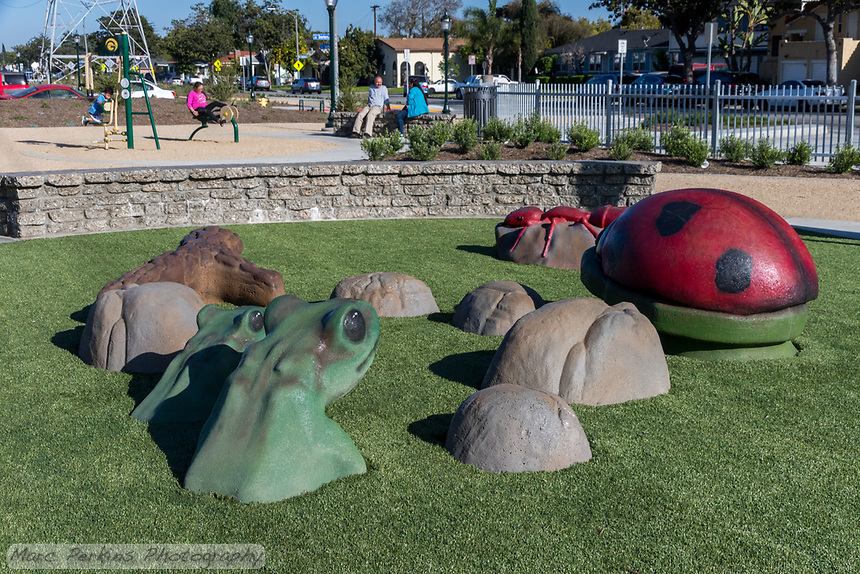 Frogs, a lady bird beetle, and an ant climbing structure on artificial turf at State Street Park while a family uses the exercise equpiment and bench in the background.