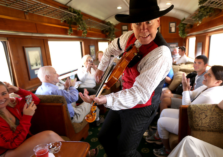 United States Senator John McCain, at left in blue and his wife Cindy, enjoy the entertainment with other passengers as a fiddle player works his magic on the train to the Grand Canyon out of Williams, Arizona Wednesday morning. (Photograph by Daniel A. Anderson)
