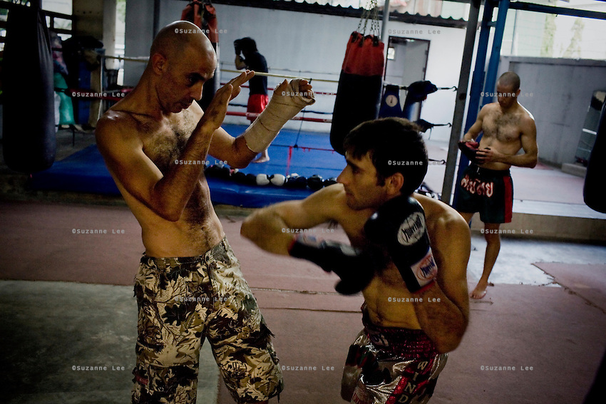 "Shuki (left) coaches Gili (2nd from right) as Eran (right) takes a break in Rompo Muay Thai Gym, Khlong Toei, Bangkok city, Thailand on 14th December 2009..Shuki Rosenzweig, aged 40, is a professional Muay Thai Boxing fighter (champion) and trainer who has lived for 9 years in Thailand. He is famous in Israel as the authority of this sport. Started at the age of 12 in boxing in Israel, Jerusalem. Used to work in the fish market. His father is a 'legend' in Jerusalem fish market. Shuki stopped working with his dad about 13 years ago. He has opened some muay thai gyms in Thailand in the past. He currently has about 5 Israeli fighters under his training in Bangkok, besides fighters of other nationalities. Shuki found religion in Bangkok with Chabad about 4 years ago. He never misses Shabbat and loves to sing the songs of prayer, priding himself with a good voice. ""Chabad integrates all Jews. it keeps us together. When at Chabad, we are at home, united with people of the same culture, language and beliefs""..Gil Saat (known affectionately as Gili), aged 29, from Ramat Gan, Israel, has been a boxer for 9 years. He is on his second trip to Thailand for muay thai. On the first trip, he stayed for 6 months, fighting in about 10 competitions in Thailand and once in Cambodia. Gili has graduated in many sport related courses from institutes in Thailand and Israel, including a diploma in Thai massage. He first met Shuki in Israel many years ago at a competition when Shuki was the trainer for Gili's opponent in the ring. A few years after that, Gili attended a seminar given by Shuki about muay thai and then decided to come to Thailand to train under him. Gili comes from a more religious family in comparison to Shuki. Gili's grand father is a rabbi in Israel. Gili introduced Shuki to Chabad (both Khao San and Sukhumvit) about 4-5 years ago and they have since spent every shabbat at Chabad. On 4th Dec 2009, they both turned up for shabbat immediately after a competition, still blee"