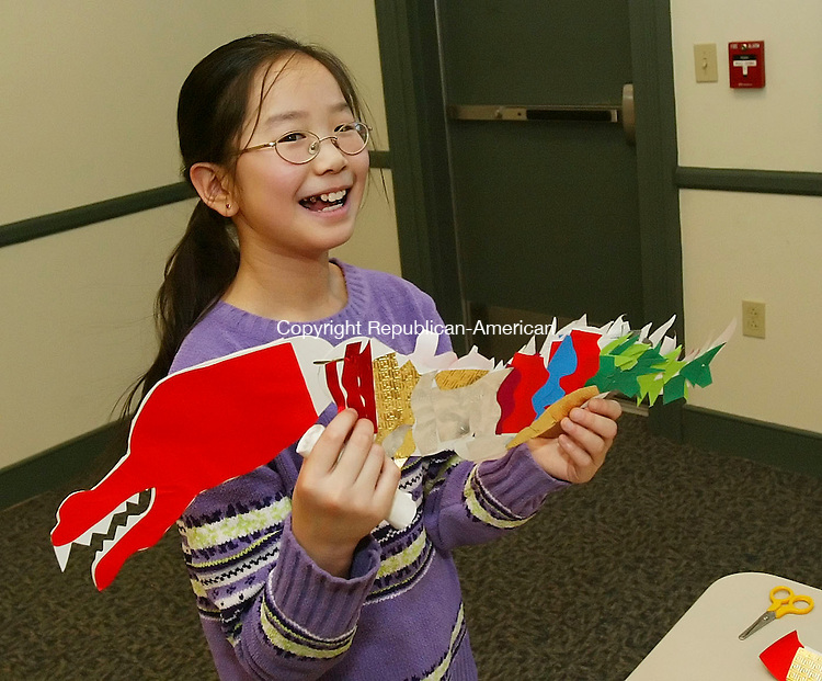 SOUTHBURY, CT, 02/09/07- 020907BZ02- Meghan  Cody, 10, gr. 5, shows the dragon she made during a Chinese New Year program at the Southbury Public Library to her mother Friday afternoon.  The Tween Craft program, for 4th and 5th graders is held once a month and is limited to 15 kids who sign up in advance.<br /> Jamison C. Bazinet Republican-American