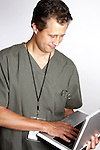 A Hawaiian ethnic man in scrubs using a laptop computer