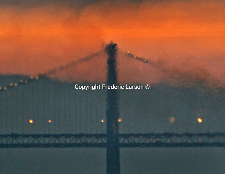 Heat wave from a tanker ship that pass by the Bay Bridge during sunrise in San Francisco's Bay, California.