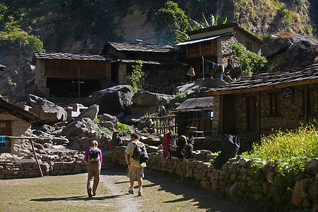 Trekkers enter a village in the Budhi Gandaki gorge - AROUND MANASLU TREK, NEPAL
