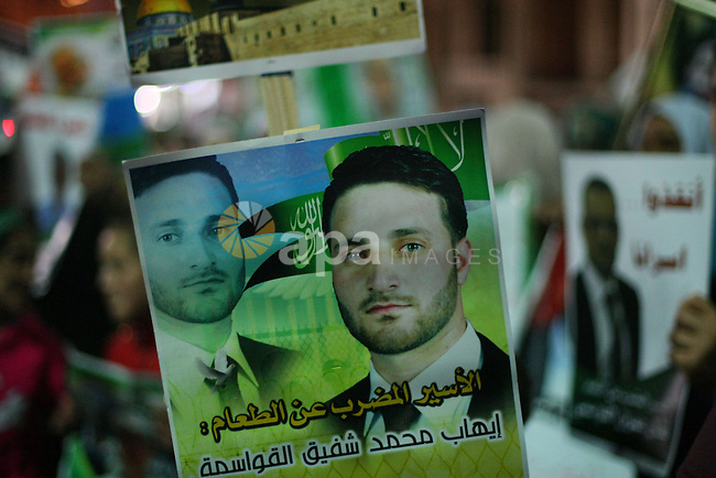 """Palestinians hold a poster of prisoners during a rally to show solidarity with Palestinian prisoners held in Israeli jails, in the West Bank city of Hebron May 13, 2014. Israel took a step on Sunday toward enacting a law that could block any future release of Palestinian prisoners convicted of killing Israelis and impede any efforts to restart frozen peace talks. Some 120 Palestinians jailed without trial in Israel have been on an open-ended hunger strike, eating only salt and drinking water, for the past 20 days to demand an end to so-called """"administrative detention"""". Photo by Mamoun Wazwaz"""