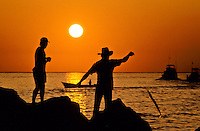 mexican fishermen landing a caught fish at the end of the line in front of the sunset