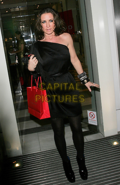 MEG MATTHEWS.The Mummy Rocks launch party at Garrards, London, England. .March 18th 2009.full length black tights one shoulder dress red bag.CAP/AH.©Adam Houghton/Capital Pictures.